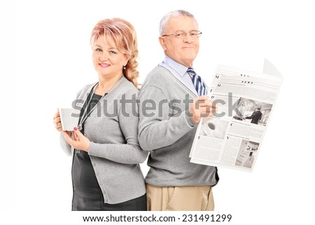 Mature couple with a newspaper and cup of coffee isolated on white background - stock photo