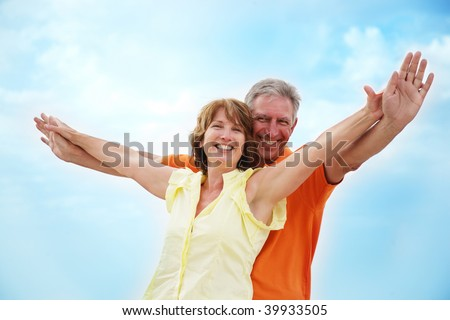 Mature couple with arms outstretched over a blue sky background - stock photo
