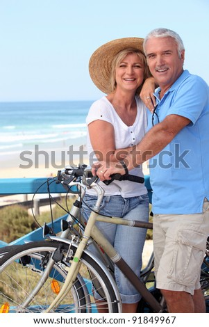 Mature couple with bikes by a beach - stock photo