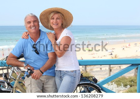 Mature couple with bikes by the beach - stock photo