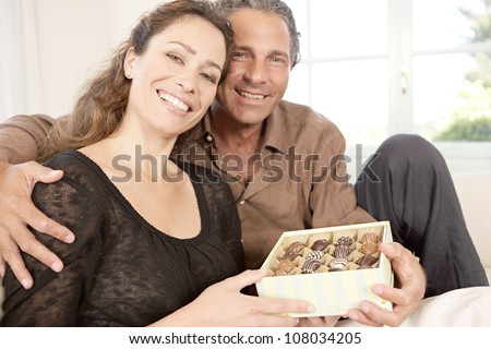 Mature couple with box of chocolates at home. - stock photo