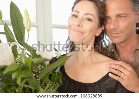 Mature couple with bunch of flowers at home. - stock photo