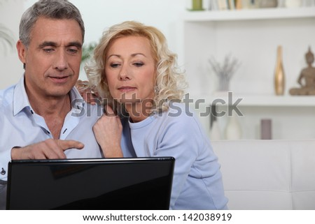 Mature couple with computer - stock photo