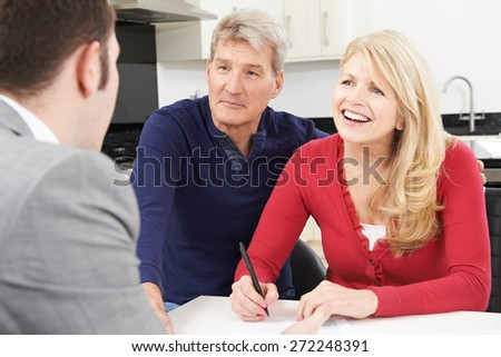 Mature Couple With Financial Advisor Signing Document At Home - stock photo