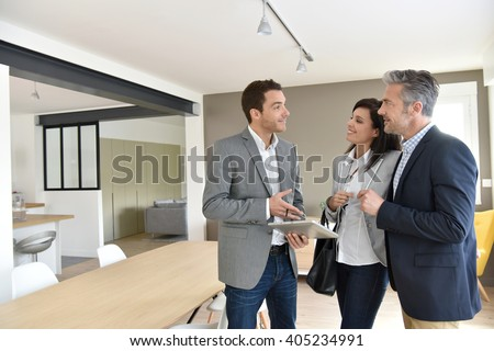 Mature couple with real-estate agent visiting new house - stock photo