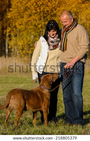 Mature couple with retriever dog embracing in autumn sunny park - stock photo