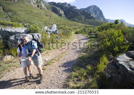 Mature couple, with rucksacks, hiking on mountain trail, looking at map, man leaning on hiking pole - stock photo