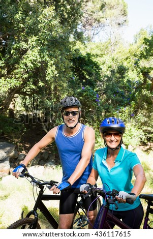 Mature couple with sunglasses posing with their bikes on the wood - stock photo