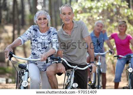 Mature couples on a double date biking. - stock photo