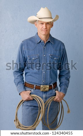 Mature cowboy against blue background in denim jeans and denim shirt holding a rope looking to camera - stock photo