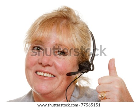 Mature customer service representative with headset gives thumbs up - stock photo