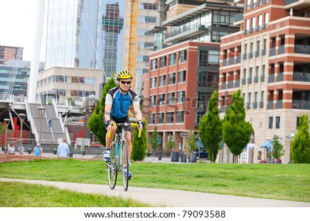 Mature cyclist in city park - stock photo