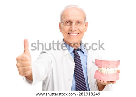 Mature dentist holding a big denture and giving a thumb up isolated on white background - stock photo