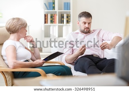 Mature depressed man on psychotherapy session at home - stock photo