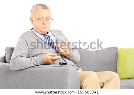 Mature diabetic patient seated on a sofa measuring sugar level in blood using glucometer isolated on white background - stock photo