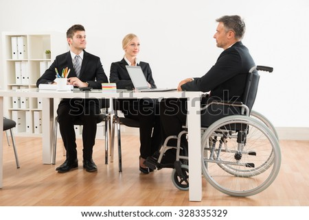 Mature Disabled Businessman Discussing With His Co-workers In Office - stock photo
