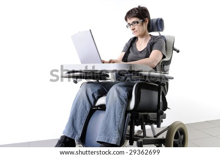 Mature disabled woman working on a laptop in a wheelchair - stock photo