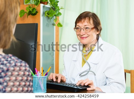 mature  doctor and patient  in a doctor's office - stock photo