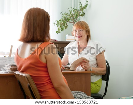 Mature doctor and pregnant woman in clinic