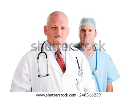 Mature doctor and younger, surgical intern.  Medical team with serious expressions.  Isolated on white.   - stock photo