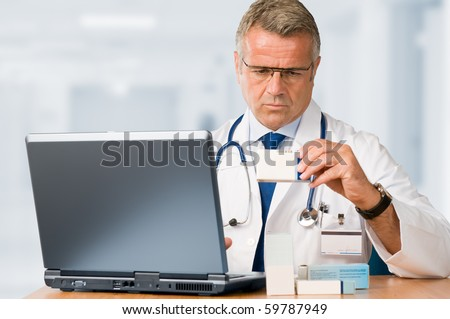 Mature doctor examining a medication's case to make prescriptions in his clinic office *Please note: the Doctor Label is made by myself with a personal design* - stock photo