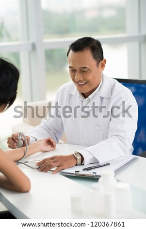 Mature doctor examining blood pressure of patient