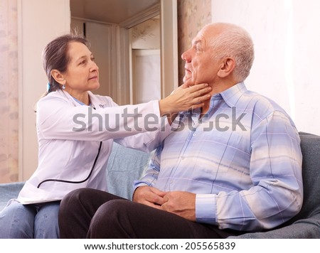 mature doctor examining senior man at home - stock photo