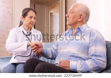 mature doctor examining senior man on couch at home - stock photo