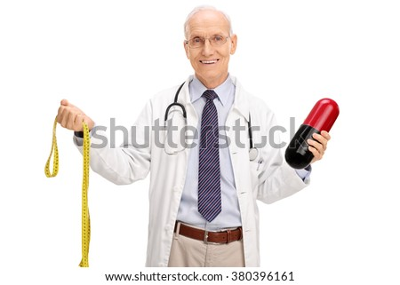 Mature doctor holding a huge diet pill and holding a yellow measuring tape isolated on white background - stock photo