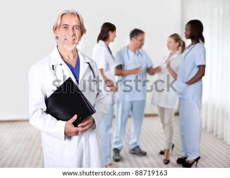Mature doctor holding files with a group of doctors discussing behind