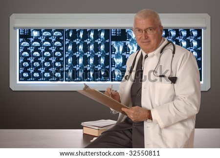 Mature doctor sitting on a desk with MRI films in the background - stock photo