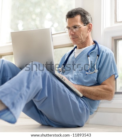 Mature doctor sitting on floor, leaning against wall, in blue scrubs, working on his laptop - stock photo