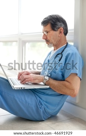 Mature doctor sitting on floor reviewing data on his laptop computer. Light and bright exposure. - stock photo