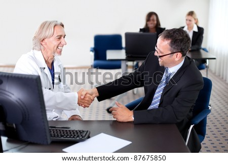 Mature doctor smiling and shaking hands with a patient at his desk in his office - colleagues in the background