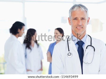 Mature doctor standing upright in front of his interns