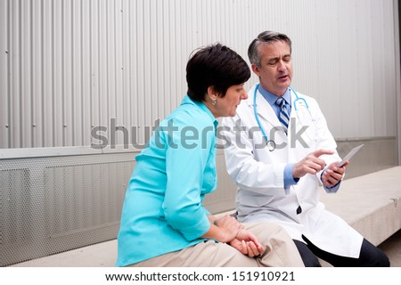 mature doctor with female patient at hospital - stock photo