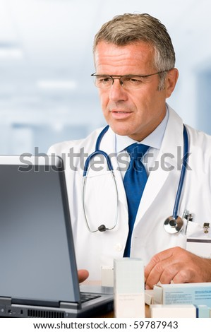 Mature doctor working on laptop and making medication's prescriptions in his clinic office - stock photo