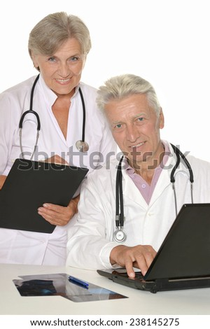 Mature doctors with a laptop on a white background - stock photo
