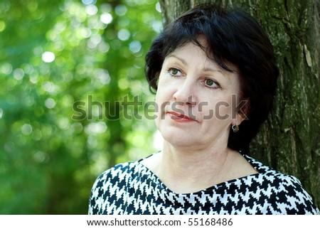 Mature dreamy woman in the park - stock photo