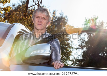 Mature driver standing near the car with opened door and sunlight on background - stock photo