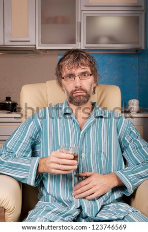mature drunk man sitting in chair with glass - stock photo