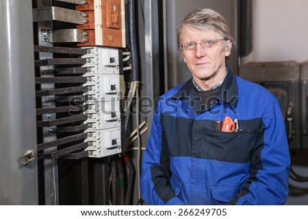 Mature electrician worker standing near high voltage panel - stock photo