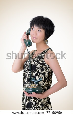 Mature elegant Asian woman holding old cellphone, closeup portrait on studio background. - stock photo