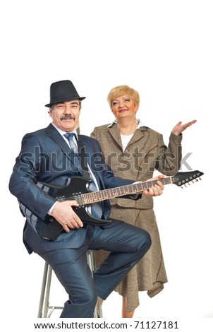 Mature elegant guitarist playing guitar and his wife smiling isolated on white background - stock photo