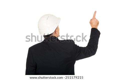 Mature engineer with hard hat pointing up. - stock photo