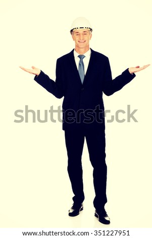 Mature engineer with hard holding copyspace in both hands. - stock photo