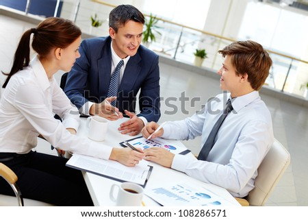 Mature entrepreneur sharing experience with the next generation of business people - stock photo