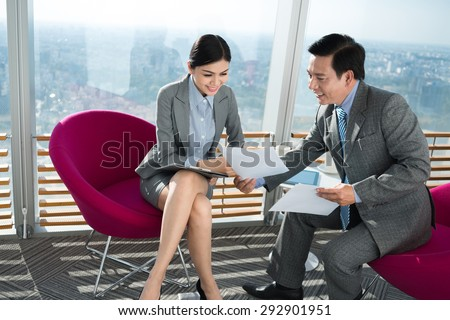 Mature entrepreneur showing documents to his young business partner - stock photo