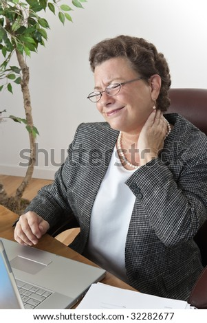 Mature executive businesswoman at her desk with a pain in the neck and headache, wincing and rubbing her neck - stock photo