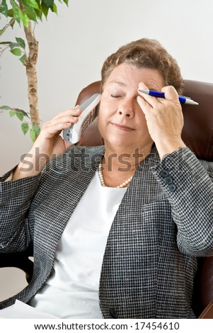 Mature executive type businesswoman with eyes closed with a headache.